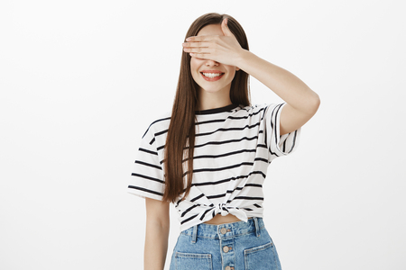 Waiting to see what her dear friends prepared. Studio shot of attractive intrigued woman in trendy striped t-shirt, covering eyes with palm and smiling happily, feeling great on surprise party