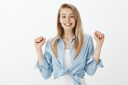Portrait of cute excited european female student with blond hair, raising clenched fists and smiling cheerfully, feeling great and happy, hearing results of event, celebrating success over gray wall Фото со стока