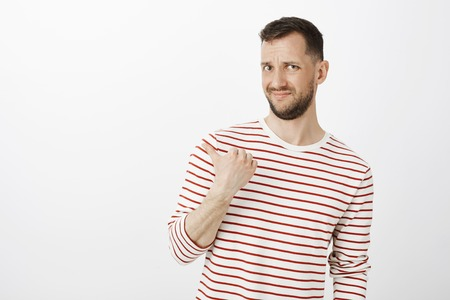 Who invited that guy. Portrait of displeased doubtful attractive male in striped pullover, grimacing from disgust and pointing left with thumb, being unsure, standing over gray background
