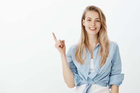 Innenaufnahme der kreativen stilvollen blonden Frau mit breitem Lächeln, das den Zeigefinger anhebt, während es auf die obere linke Ecke zeigt, eine großartige Idee oder einen Vorschlag hat und an der perfekten Stelle für den Kopierraum anzeigt