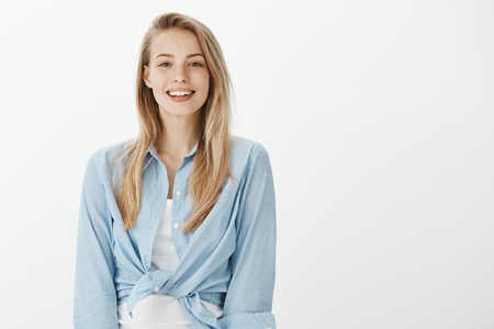 Portrait of kind charming european female student in stylish outfit, smiling friendly and happilly while gazing at camera, expressing positive, joyful attitude while talking casually over white wall