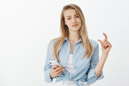Indoor shot of unimpressed displeased attractive fair-haired girl in stylish clothes, shaping something small or tiny with fingers, smirking while holding smatphone, being indifferent with size Stock Photo