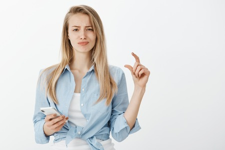 Portrat of unimpressed unhappy european woman with fair hair, shaping tiny or small thing with fingers, smirking and frowning from disappointment, holding smartphone and explaining something