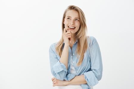 Kreative gut aussehende Designerin mit blondem Haar, beißendem Finger, aufblickend und neugierig lächelnd, während sie eine großartige Idee hat, verträumt über grauem Hintergrund steht und einen interessanten Plan hat