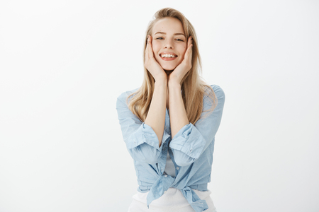 Good-looking cute female student in stylish outfit, touching face with palms gently and smiling broadly, being satisfied with result of facial mask, feeling relieved while standing over white wall