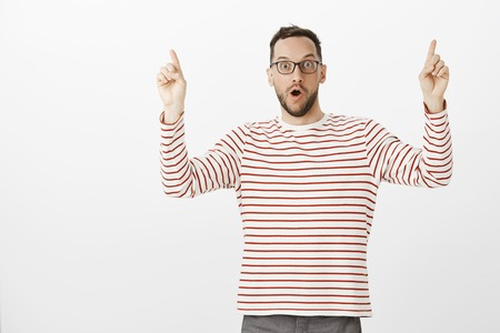 Look, it is unbelievable. Portrait of impressed excited handsome european man with bristle in glasses, raising index fingers and pointing up with shocked expression, saying wow over gray background Stock Photo