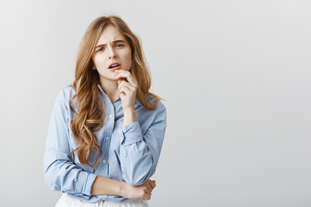 Trendy girl having doubts about new dress. Studio shot of disbelieving good-looking female student in blue-collar shirt, touching lip and staring with concerned expression, thinking over gray wall Foto de archivo