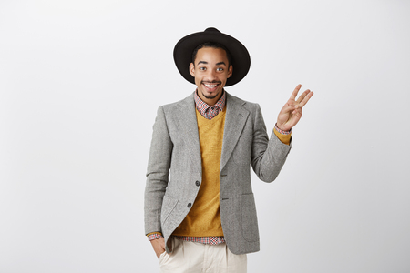 Studio shot of pleased successful african boyfriend in stylish hat and gray jacket showing number with hand and smiling broadly, giving suggestion or answering question