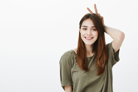 Portrait of good-looking carefree girlfriend in casual t-shirt, showing v sign behind head, mimicking bunny ears and smiling happily over gray wall
