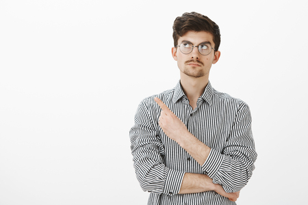 Portrait of hesitating intrigued calm guy with beard and moustache in round glasses, looking and pointing at upper left corner with curious expression, seeying something interesting over gray wall