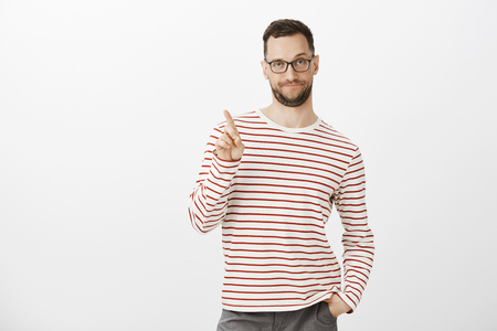 We can kiss only on third date. Unsure gay with bristle and glasses, shaking index finger in no or not yet gesture, being displeased and unimpressed, rejecting something with smirk and intrigue Stock Photo