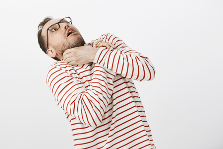 Portrait of funny european man in glasses, holding hands on neck and bending backwards, choking, mimicking attack playfully over gray wall Archivio Fotografico