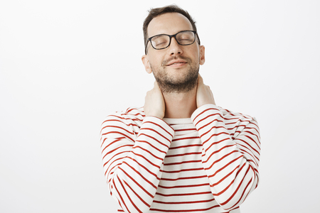 Guy recalls nice feeling of lovers hands. Sensual romantic european gay model in glasses, closing eyes and tilting head up with slight tender smile, touching neck, standing over gray background