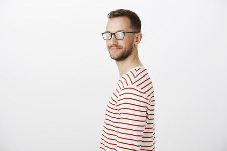 Profile portrait of friendly confident bright guy in striped pullover, turning at camera and smiling broadly, feeling relaxed and comfortable while standing against gray background casually
