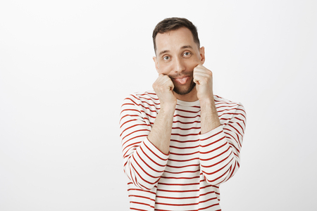 Portrait of playful childish Caucasian guy in striped clothes, pulling mouth with hands and sticking out tongue with indifferent bored expression, being tired of boring talk over gray background Stock Photo