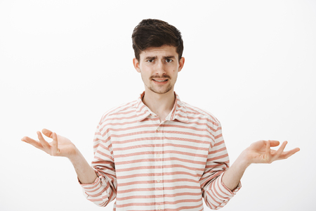 Guy listening ridiculous explanations, being clueless and unimpressed. Attractive caucasian brother with moustache and beard, spread palm and shrugging, frowning from misunderstanding, unaware Stock Photo