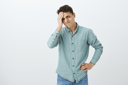 Troubled upset young man in casual shirt, holding hand on forehead and grimacing from regret, forgetting something or feeling sadness from missed chance, standing disappointed over gray wall