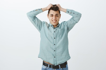 Adult coworker in casual shirt, pulling out hair and grimacing from nervousness and lack of confidence, standing insecure over gray background Stock Photo