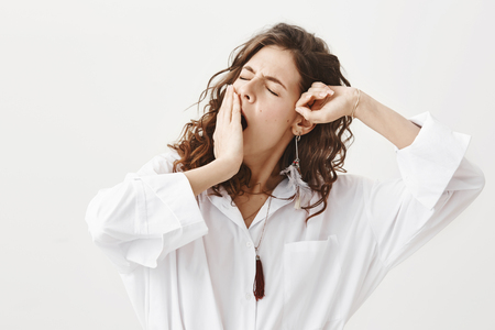 Studio portrait of tired or exhausted young businesswoman yawning and stretching while covering mouth with hand, standing with closed eyes over gray background. Girl have not got enough sleep
