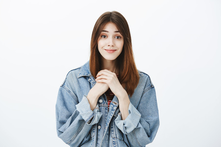 Portrait of positive adorable brunette in stylish denim jacket, clenching hands together near chest and smiling with tender and warm expression, being charmed with cuteness of kitty over gray wall Stock Photo