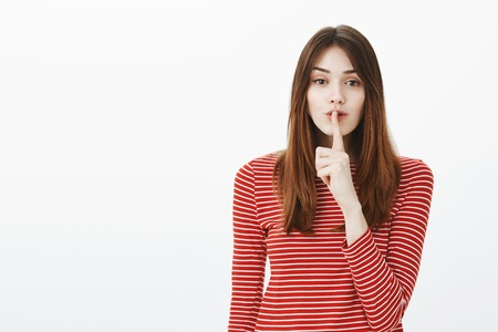 Secrets and beautiful people concept. Portrait of charming adult female student holding index finger over mouth, shushing friend, making shhh sound while asking keep voice down against gray background Stock Photo