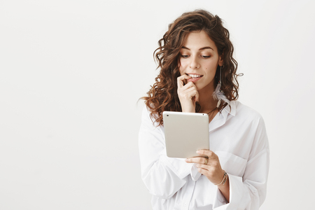 Portrait of curious intrigued beautiful woman biting finger while looking at tablet with excitement, standing over gray background. Girl thinks whether she want sent message or not Stock Photo