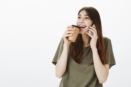Portrait of excited curious young woman in casual outfit, talking on white smartphone and making sip of coffee, smiling broadly, being intrigued and liking speaking with best friend about funny things Stock Photo