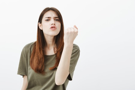 Angry girlfriend will show boyfriend how not sleep home. Portrait of threatening outraged cute young woman, shaking fist and anger and grimacing, scolding or arguing over gray background