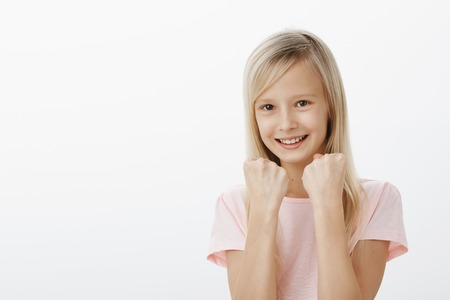 Young girl will show everyone her strengths. Studio shot of cheerful adorable daughter in pink t-shirt, raising clenched fists, standing in boxing pose, fooling around and smiling broadly, defending Archivio Fotografico