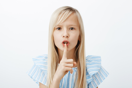 Serious obedient child asks keep voice down, looking after little sister. Confident adorable fair-haired young girl, bending towards camera, making shush sign, saying shh with index finger over mouth