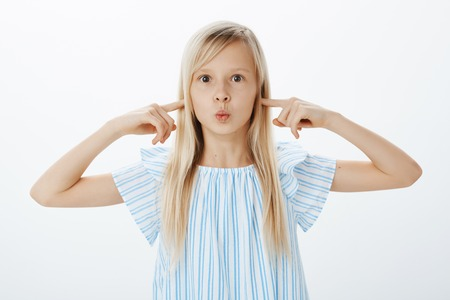 Studio shot of overwhelmed excited cute girl with blond hair, pouting with folded lips and covering ears with index fingers, being unfocused and bored, being disobedient while shopping with mom Stock Photo