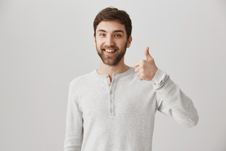 Positive emotive european employee with bright smile showing thumbs up and being in good mood while standing against gray background. Mate thinks it is great idea to play board games