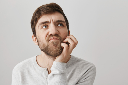 Close-up shot of confused questioned unshaven guy scratching jaw and looking aside, frowning as thinking about something problematic, standing over gray background Stock Photo