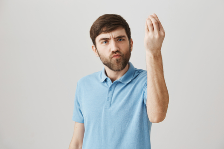 Cute bearded european male standing with raised hand and showing italian gesture and puckered lips, frowning, being serious while standing against gray background. Brother proves his point of view Banco de Imagens