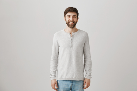 Portrait of good-looking pleasant bearded caucasian guy in loose pullover smiling broadly while standing over gray background with confident and friendly expression Stock Photo