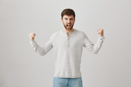 Man proves he is strong and powerful. Portrait of handsome bearded guy trying to bragg with muscles, standing with raised hands and shouting, trying to make scary face over gray background