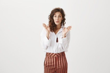 Woman feeling intrigued waiting to see surprise, smiling broadly and being happy. Attractive european female with curly hair in stylish striped trousers, smiling, folding lips, raising palms near face Stock Photo