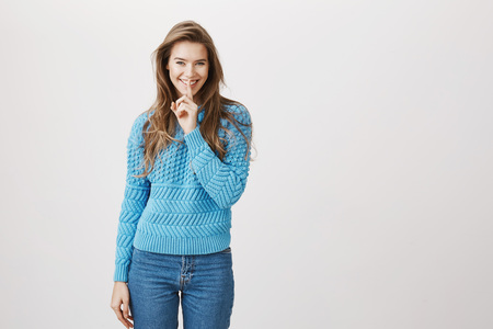 Playful charming european model holding index finger on mouth saying shh while smiling and standing against gray background. Let us keep it a secret from others. You should not tell anyone Stock fotó - 103251440