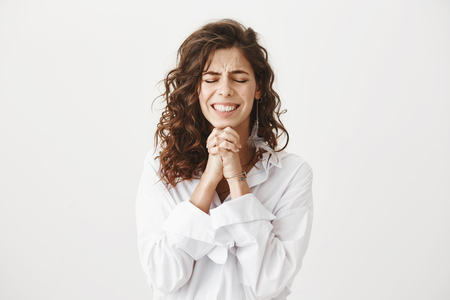 Studio shot of worried and upset caucasian woman holding hands in pray near chin, squeezing it tight and begging for something, smiling nervously and standing with closed eyes over gray background Stock Photo