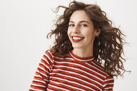Waist-up shot of carefree fashionable woman with curly hair and red lipstick, smiling broadly, gazing happily at camera. Girlfriend dressed in stylish outfit, walking to party, ready impress everyone Stock Photo