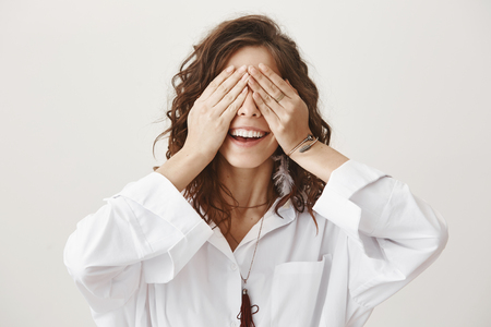 Emotive positive adult european woman covering eyes with hands and smiling broadly, being intrigued while waiting for surprise over gray background. Can I look now, what have you got for me Stock Photo