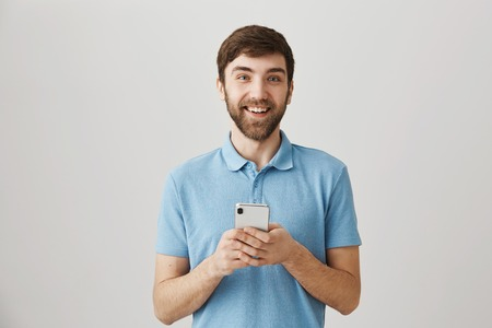 Cute adult bearded male manager smiling positively at camera while holding smartphone and messaging, standing over gray background. guy is happy his coworker finally agreed to exchange numbers Stock Photo