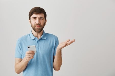 Studio shot of confused and displeased european man holding smartphone and gesturing, frowning, expressing disbelief or being puzzled with dumb question over gray background
