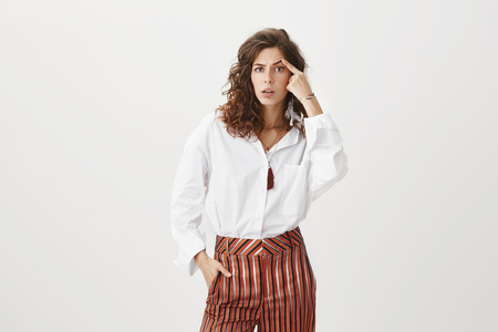 Confused intense attractive female coworker in stylish white blouse and striped pants, raising eyebrow with finger and staring clueless and questioned at camera, trying to understand what happen