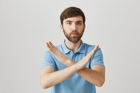 Portrait of confident serious young bearded man showing stop or decline gesture with raised crossed arms, showing his negative answer over gray background.