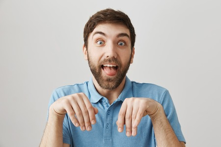 Funny european boyfriend with beard making dumb face, sticking out tongue and standing with folded hands over gray wall as if he is puppy Foto de archivo