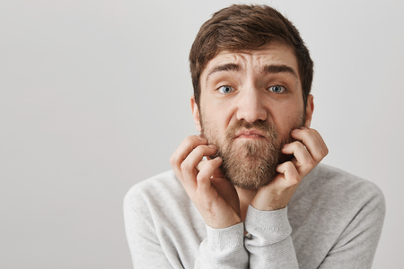 Close-up portrait of clumsy unshaven adult man scratching beard while looking with unsatisfied look at camera as if it is mirror, standing against gray background. Guy thinks he should shave