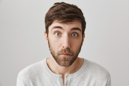 Close-up portrait of surprised and upset european male with beard standing with lifted eyebrows, clueless and tired expression over gray background. Guy is shocked to hear sad news