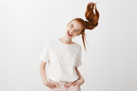 Portrait of good-looking carefree caucasian woman with red hair, tilting head and smiling joyfully, having fun over gray background, holding hand in pocket Stock Photo