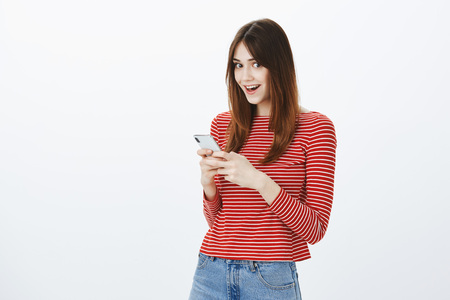 Intrigued excited woman wants to share interesting news. Portrait of pleased thrilled caucasian girlfriend in casual outfit, standing half-turned happy, holding smartphone, finding out curious rumor Stock Photo